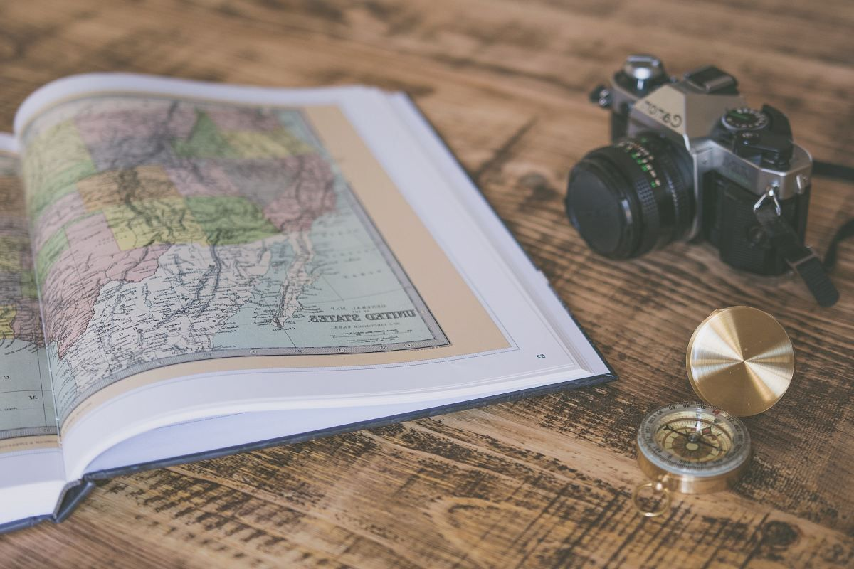 compass-with-map-on-table-camera-travel